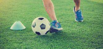 Gracz piłki nożnej stawiający błękitni sportów buty jogging z oklepa i kontroli futbolem między szyszkowymi markierami zdjęcie royalty free