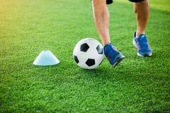 Gracz piłki nożnej stawiający błękitni sportów buty jogging z oklepa i kontroli futbolem między szyszkowymi markierami zdjęcie stock