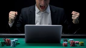 Gracz uprawia hazard na laptopie i krzyczy w podnieceniu, wygrywać zakładam się, pomyślność zdjęcie royalty free