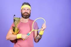 Gracz w tenisa wygrany mistrzostwo Atleta chwyta tenisowy kant i z?ota czara Wygrana tenisa gra M??czyzna modnisia brodata odzie? zdjęcia stock