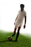 Gracza futbolu wynika cele na trawie z białym tłem Zdjęcie Royalty Free