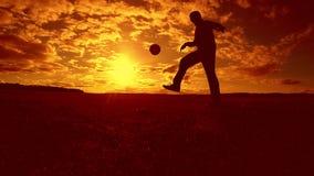 Gracza piłki nożnej farszu sylwetki balowy mężczyzna kopie piłkę w lotniczym stylu życia z zmierzchu tłem mężczyzna bawić się pił zbiory wideo