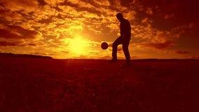 Gracza piłki nożnej farszu sylwetki balowy mężczyzna kopie piłkę w powietrzu z zmierzchu tłem mężczyzna bawić się piłkę nożną prz zbiory