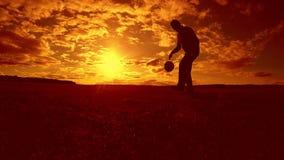 Gracza piłki nożnej farszu sylwetki balowy mężczyzna kopie piłkę w stylu życia powietrze z zmierzchu tłem mężczyzna bawić się pił zbiory