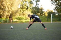 Gracza piłki nożnej rozciągania noga na śródpolnym futbolu fotografia stock