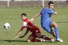 Gracze futbolu walczy dla piłki obrazy stock
