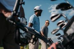 Gracze iść pole golfowe, torba z klubami przy przedpolem Zdjęcia Royalty Free