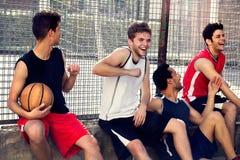 Gracze koszykówki biorą przerwy obsiadanie na depresji ścianie Obraz Royalty Free