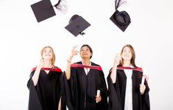 Gradúa los casquillos de la graduación que lanzan Fotografía de archivo