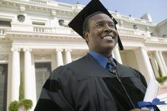 Gradúe con el diploma fuera de la opinión de ángulo bajo de la universidad Foto de archivo libre de regalías