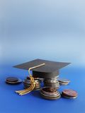 Grad cap and coins Royalty Free Stock Image