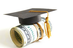 Grad money. Mini graduation cap on a roll of money Stock Image