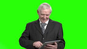 Graddad in suit swiping and sliding screen using finger. Old business man in suit using tablet pc in green hroma background stock footage