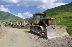 Grade builder and unesco village Usghuli. Buldozer in front of UNESCO heritage site - Usghuli, Svaneti  in Georgia Stock Photography
