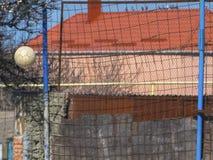 Grade da bola e do metal de futebol do voo no fundo Foto de Stock Royalty Free