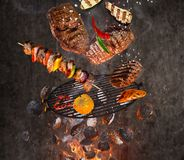 Grade da chaleira com os carvões amassados quentes, a grelha do ferro fundido e as carnes saborosos voando no ar foto de stock royalty free