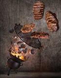 Grade da chaleira com os carvões amassados quentes, a grelha do ferro fundido e os bifes saborosos voando no ar foto de stock