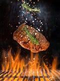 Grade da chaleira com os carvões amassados quentes, a grelha do ferro fundido e os bifes saborosos voando no ar foto de stock royalty free