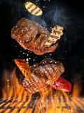 Grade da chaleira com os carvões amassados quentes, a grelha do ferro fundido e os bifes saborosos voando no ar imagem de stock