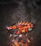 Grade da chaleira com os carvões amassados quentes, a grelha do ferro fundido e os espetos saborosos voando no ar imagem de stock