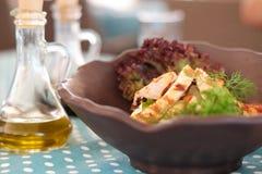 Grade da galinha em uma bacia de salada com azeite foto de stock royalty free