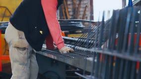 Grade de dobra do operário das barras de aço O trabalhador dobra o metal na fábrica vídeos de arquivo