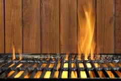 Grade do BBQ e parede flamejantes vazias da madeira no fundo fotos de stock