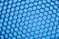 Grade do favo de mel contra o fundo azul Imagens de Stock Royalty Free