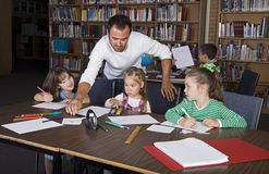 Grade School. A teacher with his elementary students in the school library Royalty Free Stock Image