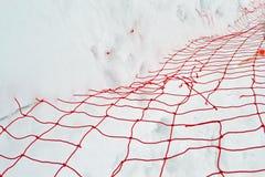Grade vermelha danificada sob a neve branca, estação do fio do inverno, Foto de Stock