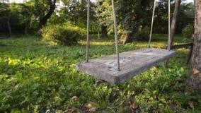 Graden swing by evening. Shaking garden swing closeup by summer evening, pan camera movement stock video