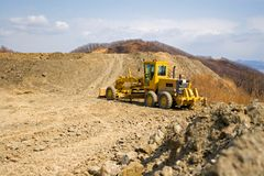Grader. The new road in mountains is laid Royalty Free Stock Photography