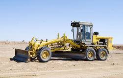Grader. A construction vehicle flattening a field Royalty Free Stock Image