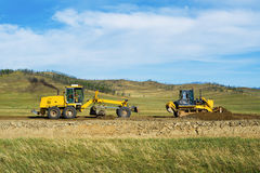 Grader and bulldozer on the construction of the road Stock Image