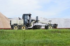 The grader is at the dam with pipeline in the background of mine. Side view. Foreground green grass stock images