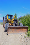 Grader on dusty gravel road Royalty Free Stock Photography