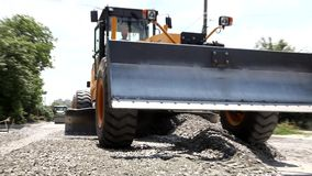 Grader excavator spread the crushed stone on the road stock footage