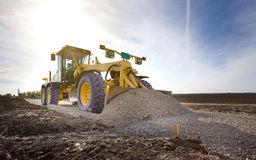 Grader working on gravel leveling Royalty Free Stock Photography