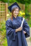 Graderad ung kvinna som ler på kameran arkivfoton