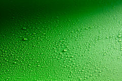 Gradient background with rain drops spread across. Shiny green surface and lit from one side Stock Image