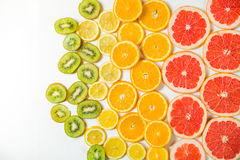 Gradient color citrus slices on white background. Gradient citrus slices - grapefruit, orange, lemon and kiwi slices, placed on white background from left to Royalty Free Stock Images