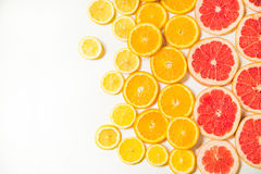 Gradient color citrus slices on white background. Gradient citrus slices - grapefruit, orange and lemon, placed on white background from left to right, from big stock photos