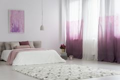 Gradient curtains in bright bedroom. With patterned carpet and pink painting on the wall above bed Royalty Free Stock Photography