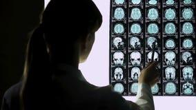 Grado calcolatore del giovane neurochirurgo di sbattimento del cervello dei pazienti sulle risonanze magnetiche archivi video