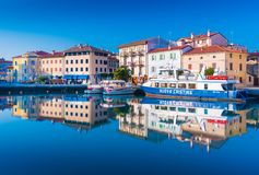 Grado, Italy: Colored residential buildings and boats are mirror reflected in sea water Stock Photos
