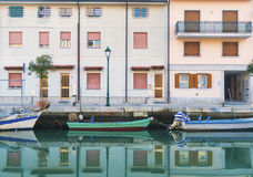 Grado, Italy - December 2015: Colored boats on the water in one of the canals of Grado Royalty Free Stock Photo