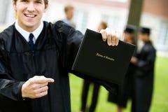 Graduação: Estudante entusiasmado Points no diploma foto de stock royalty free