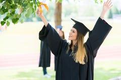 Graduação: Estudante Standing With Diploma com amigos atrás Fotografia de Stock