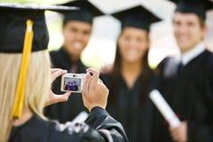 Graduação: A menina toma a foto dos amigos fotografia de stock