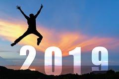 Graduación de salto de la enhorabuena del hombre feliz de la silueta en la Feliz Año Nuevo 2019 foto de archivo libre de regalías